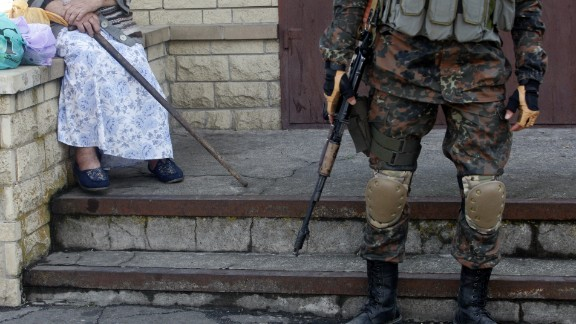 An elderly woman sits next to a Ukrainian soldier standing guard in Volnovakha on September 11.