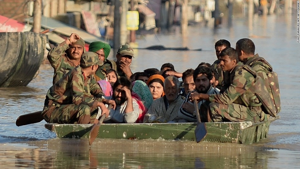 Flood-affected Kashmiri residents ride on an Indian Army raft in Srinagar on September 11.