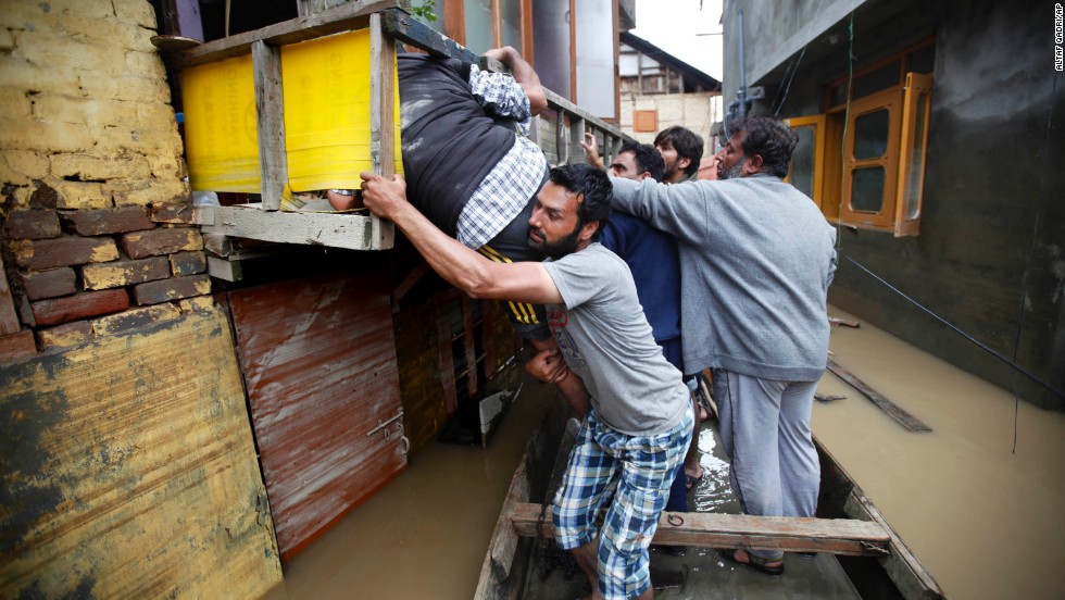 Volunteers help a flood victim from an alley in the city center of Srinagar on Friday, September 12.