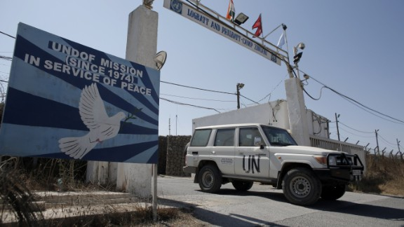File: A UN peacekeeping car leaves the main UN headquarters next to the Quneitra crossing, the only border crossing between Israel and Syria, on August 30, 2014.