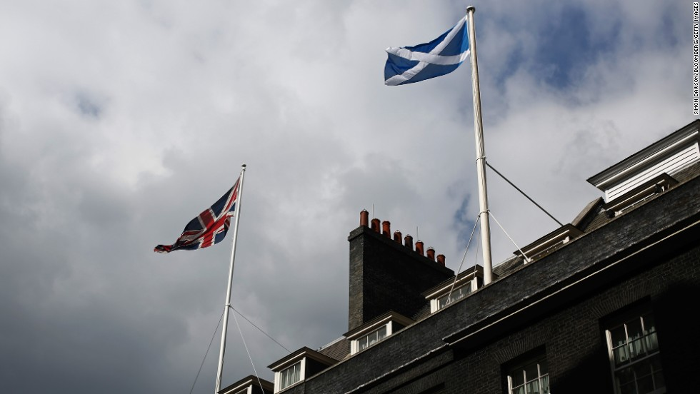 The national flag of the United Kingdom, left, and the national flag of Scotland fly above buildings on Downing Street in London.