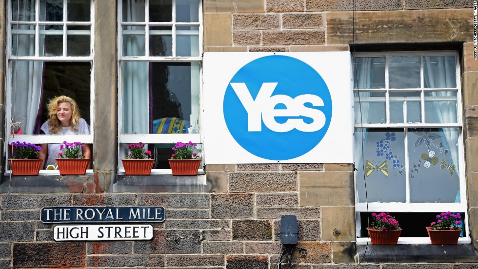 "A woman looks from a window next to a ""yes"" campaign sign in Edinburgh on Tuesday, September 9."