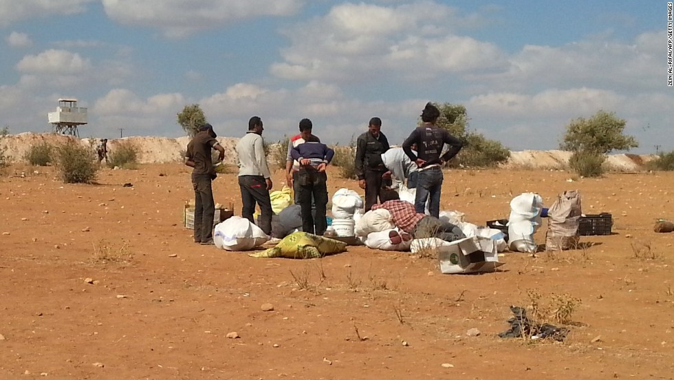 Syrians fleeing the violence stand next to their belongings as they attempt to cross into Turkey on Sunday, September 7.
