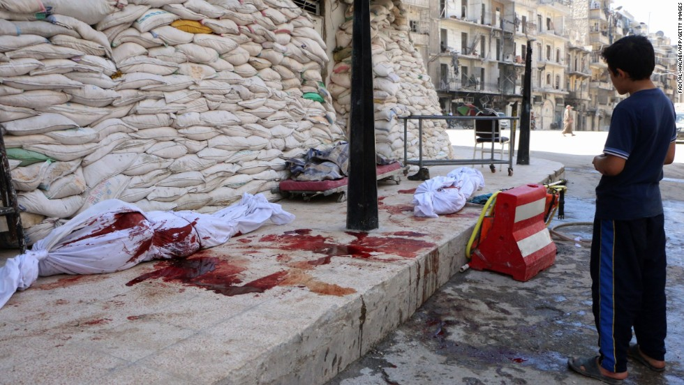 A boy looks at bodies lying outside a hospital after a barrel-bomb attack in Aleppo on Friday, September 5.