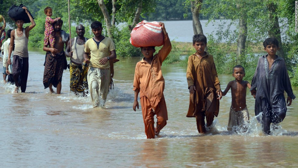 Residents wade through floodwaters Saturday, September 13, in Sher Shah, Pakistan.