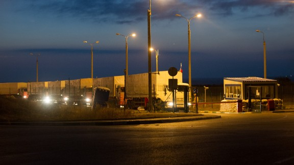 Russian trucks, flying Russian flags and carrying humanitarian aid for eastern Ukraine, line up at a border checkpoint in Donetsk on September 13.