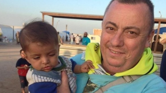 Alan Henning holds a child at a refugee camp on the Syria-Turkey border in this photo provided by his family.