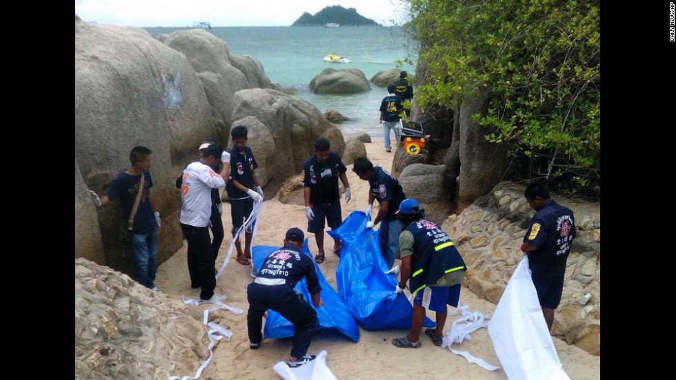 Police work near the bodies after they were found on the beach.