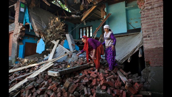 Women salvage what they can Monday, September 15, from a house destroyed by flooding in a village south of Srinagar, India. Nearly 500 people have been killed in flooding caused by intense monsoon rains across northern India and Pakistan. Thousands have been stranded.