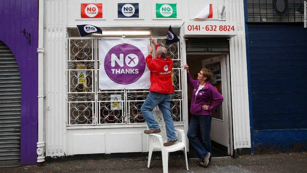 "A man hangs a banner on a ""Better Together"" campaign office in Glasgow on September 15."