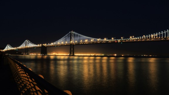 "The San Francisco-Oakland Bay Bridge illuminates the San Francisco Bay in California. Paul Heller, who shot this photo in November 2013, described it as ""a beautiful scene."""
