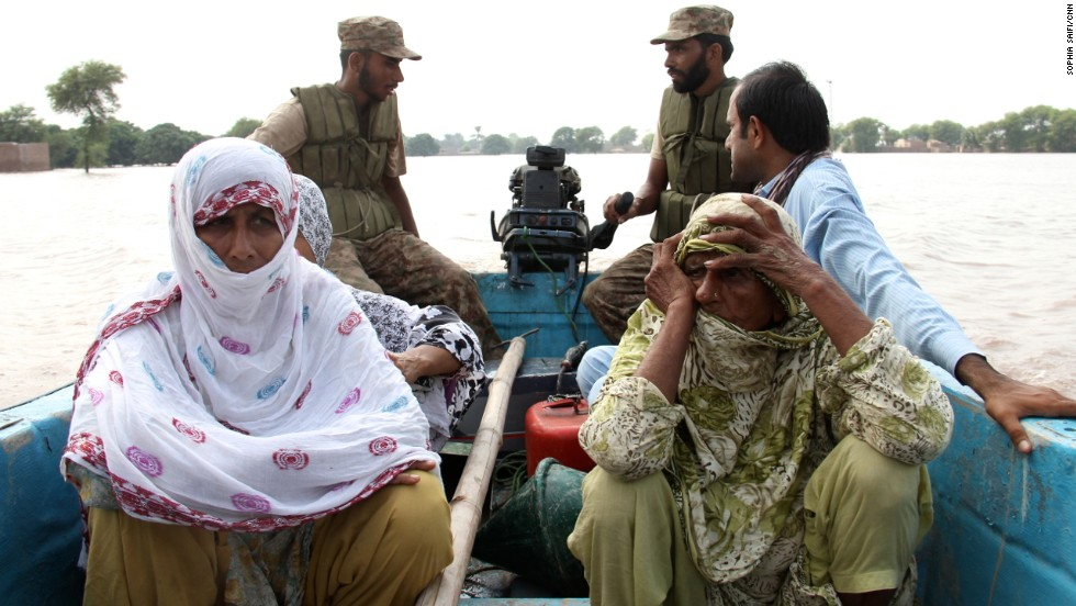 People ride in a military rescue boat after leaving their homes near Multan on September 13.