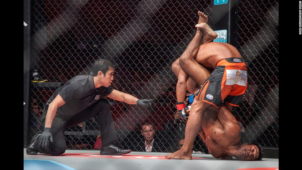 Sam Ang Dun, top, competes against Chin Heng during a mixed martial arts bout Friday, September 12, in Phnom Penh, Cambodia. Dun won by technical knockout in the first round.