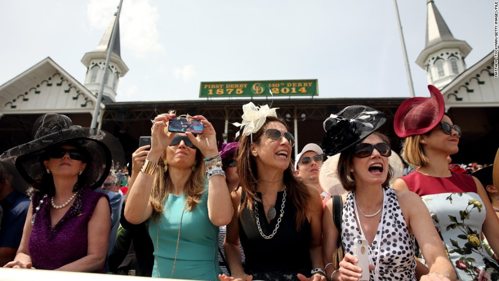 Race fans wearing festive hats cheer prior to the 140th running of the Kentucky Derby at Churchill Downs on May 3, 2014 in Louisville, Kentucky.