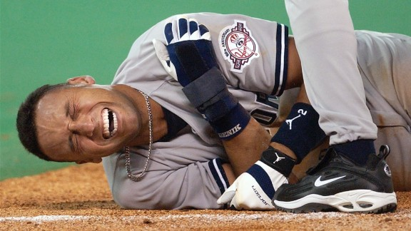 Jeter grimaces after a third-base collision in Toronto in March 2003. Jeter hurt his shoulder and went on the disabled list. It was one of the few times in Jeter