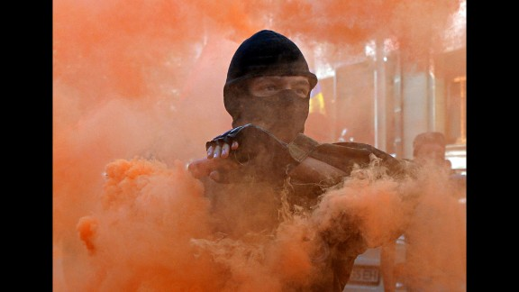 A protester holds a smoke bomb during a demonstration outside the Presidential Palace in Kiev, Ukraine, on September 17. Activists protested the adoption of legislation giving greater autonomy to rebel-held parts of eastern Ukraine