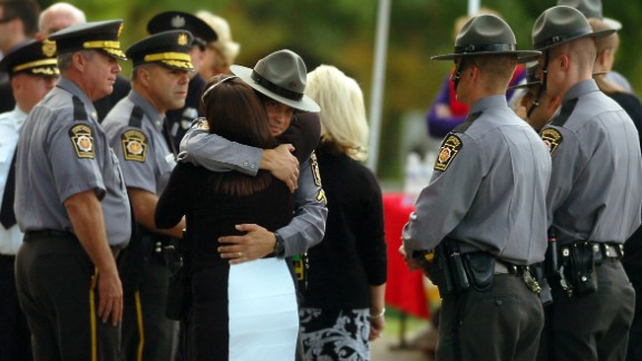 A woman embraces a Pennsylvania state trooper during the viewing of Dickson