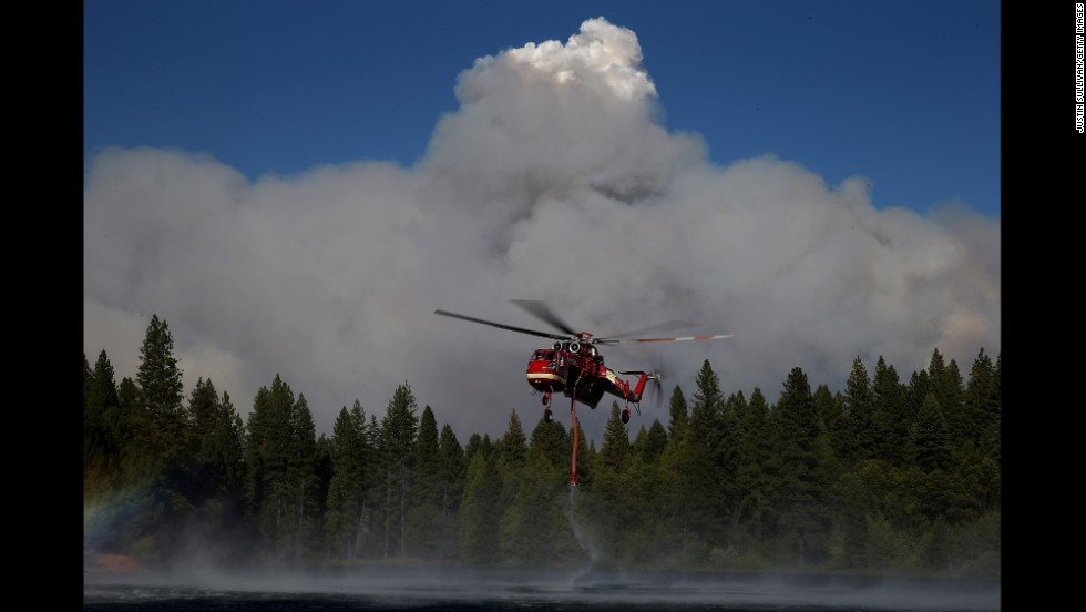 A firefighting helicopter collects water from a reservoir in Pollock Pines on September 17.