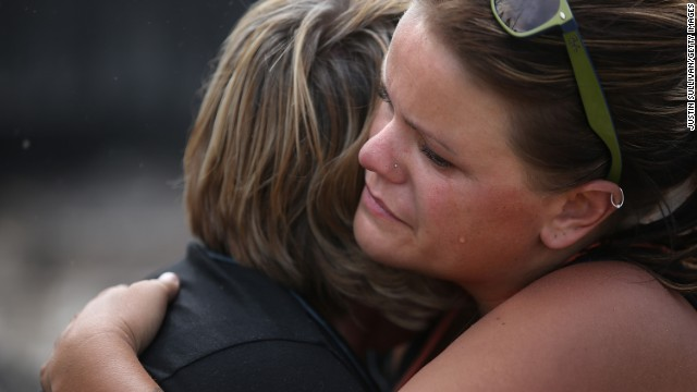 Shelley Besk, right, embraces her mother, Kathy Besk, as they stand in the burned-out ruins of their Weed home.