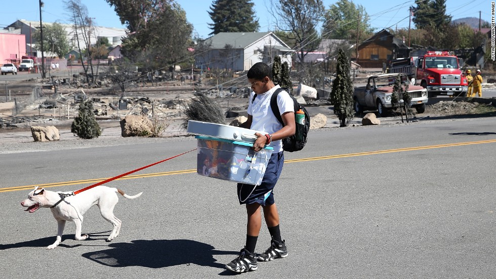A resident of Weed carries belongings as he walks by burned-out homes on September 16.
