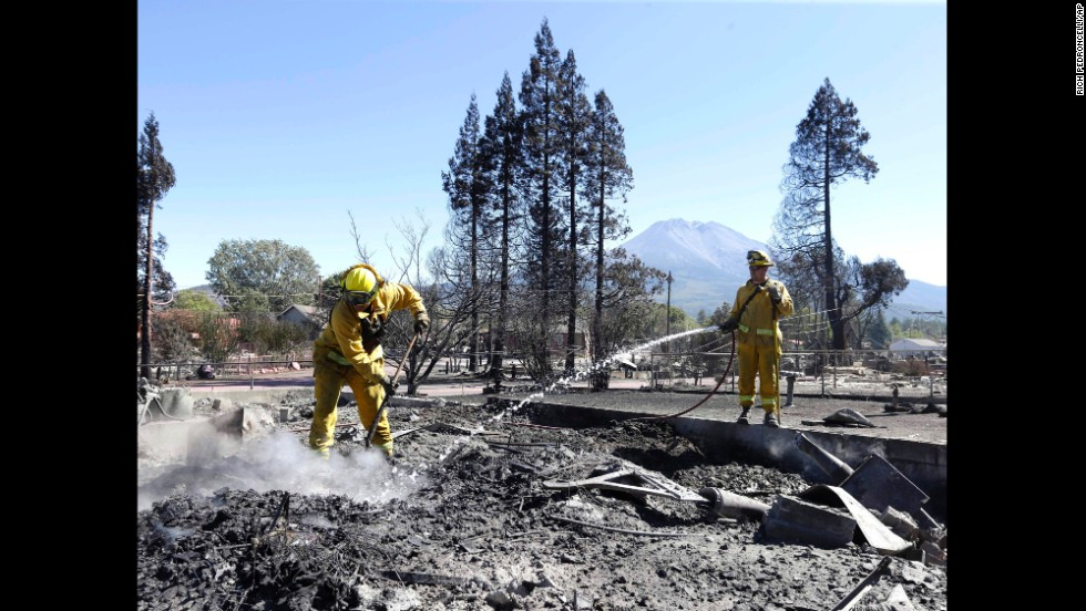Firefighters hose down a hot spot September 16 in the rubble of a Weed home.