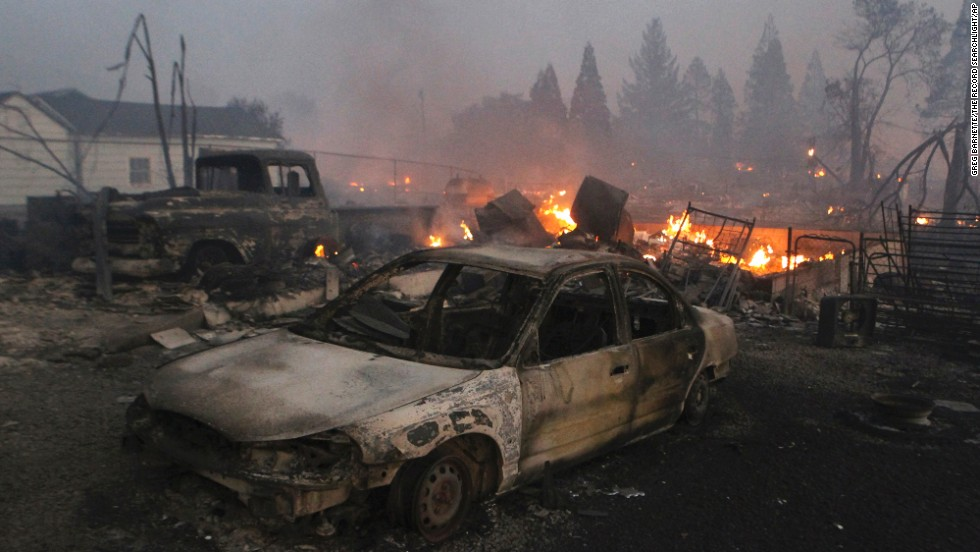 Destroyed vehicles and homes smolder in Weed on Monday, September 15.
