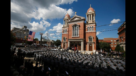 An honor guard carries the casket of Cpl. Bryon K. Dickson, a Pennsylvania state trooper, from his funeral service Thursday, September 18, in Scranton, Pennsylvania. Dickson was one of two state troopers shot last week while they were leaving their police barracks in Blooming Grove, Pennsylvania. The other trooper, Alex T. Douglass, was severely wounded.