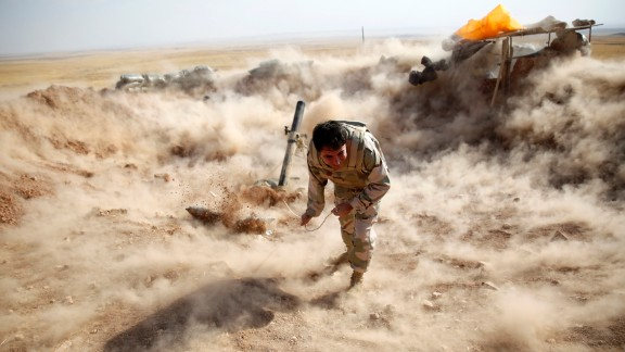 A Kurdish Peshmerga fighter launches mortar shells toward ISIS militants in Zumar, Iraq, on Monday, September 15.