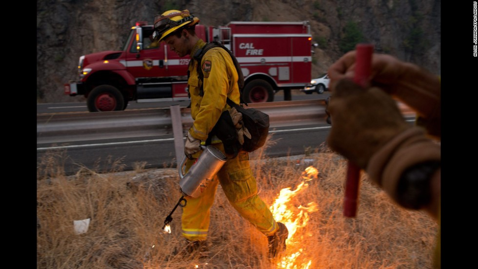 Firefighters use a drip torch to burn away excess dry brush during controlled fire operations near Pollock Pines, California, on September 18.
