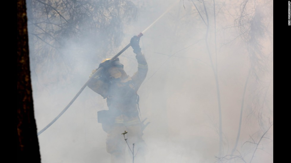 A firefighter waters down a tree as flames approach a containment line near Fresh Pond, California, on September 18.
