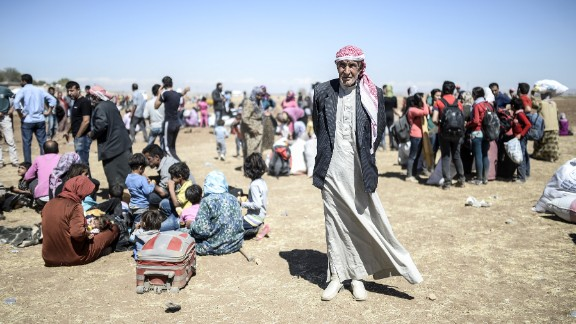 Caption:Syrian Kurds rest after crossing the border between Syria and Turkey near the southeastern town of Suruc in Sanliurfa province, on September 20, 2014. A man carries an elderly Syrian Kurd after they crossed the border between Syria and Turkey near the southeastern town of Suruc in Sanliurfa province, on September 20, 2014. Several thousand Syrian Kurds began crossing into Turkey on September 19 fleeing Islamic State fighters who advanced into their villages, prompting warnings of massacres from Kurdish leaders. Turkey on September 19 reopened its border with Syria to Kurds fleeing Islamic State (IS) militants, saying a