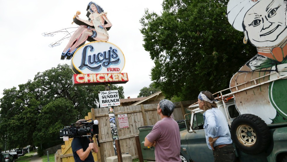 "Evan Voyles shows Rowe the sign he made for ""Lucy's Fried Chicken."" Volyes runs ""The Neon Jungle,"" a sign making business in Austin, Texas."