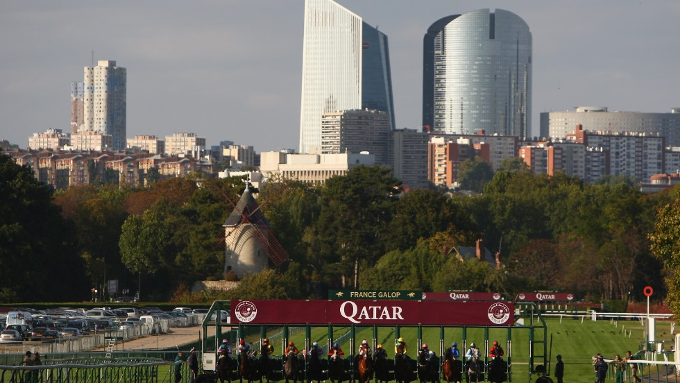 The backdrop of Paris' financial district looms in the distance behind the race start at Longchamp.