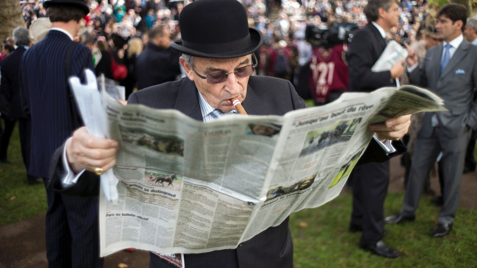 An elderly punter checks the newspaper form on race day at the Prix de l'Arc de Triomphe.
