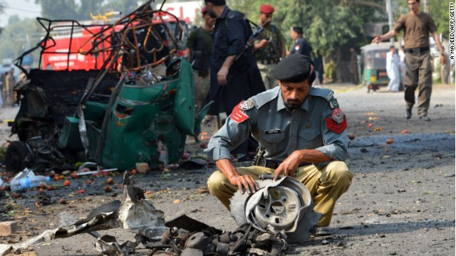 Pakistani police officials examine mangled wreckage at the site of a suicide bomb attack in Peshawar.