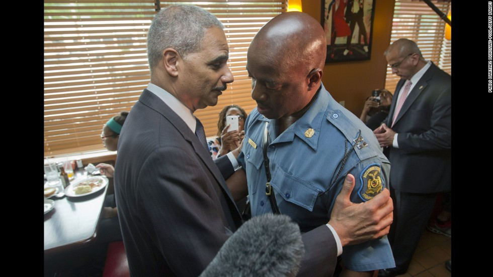 Holder talks with Capt. Ron Johnson of the Missouri State Highway Patrol in Ferguson, Missouri, in August 2014. Holder traveled to Ferguson to oversee the federal government's investigation into a police officer's shooting of 18-year-old Michael Brown.