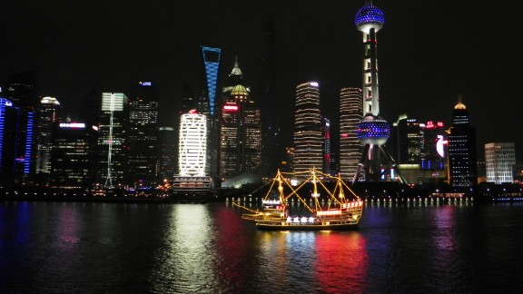 The vibrant glow of Pudong, a waterfront area in central Shanghai, reflects against the calm waters of China