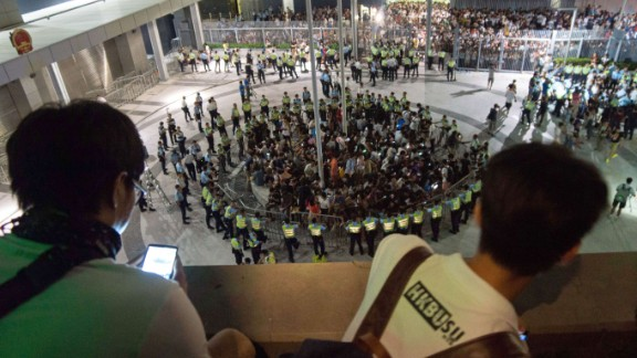 People watch from on high as pro-democracy demonstrators are surrounded by police after storming a courtyard outside Hong Kong