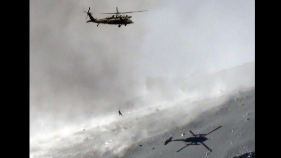 A Japan Self Defence Force helicopter lifts a survivor from the volcanic ash covered top of Mount Ontake.