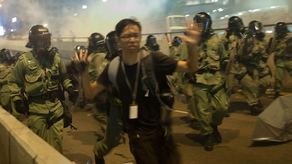 "Demonstrators disperse as tear gas is fired during a protest on September 28. There is an ""optimal amount of police officers dispersed"" around the scene, a Hong Kong police representative said."