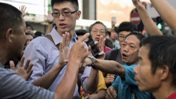 Pro-democracy protesters argue with a man (L) opposing their occupation of Nathan Road, a major route through the heart of the Kowloon district of Hong Kong, on September 29, 2014. Police fired tear gas as tens of thousands of pro-democracy demonstrators brought parts of central Hong Kong to a standstill on September 28, in a dramatic escalation of protests that have gripped the semi-autonomous Chinese city for days. AFP PHOTO / ALEX OGLE (Photo credit should read Alex Ogle/AFP/Getty Images)