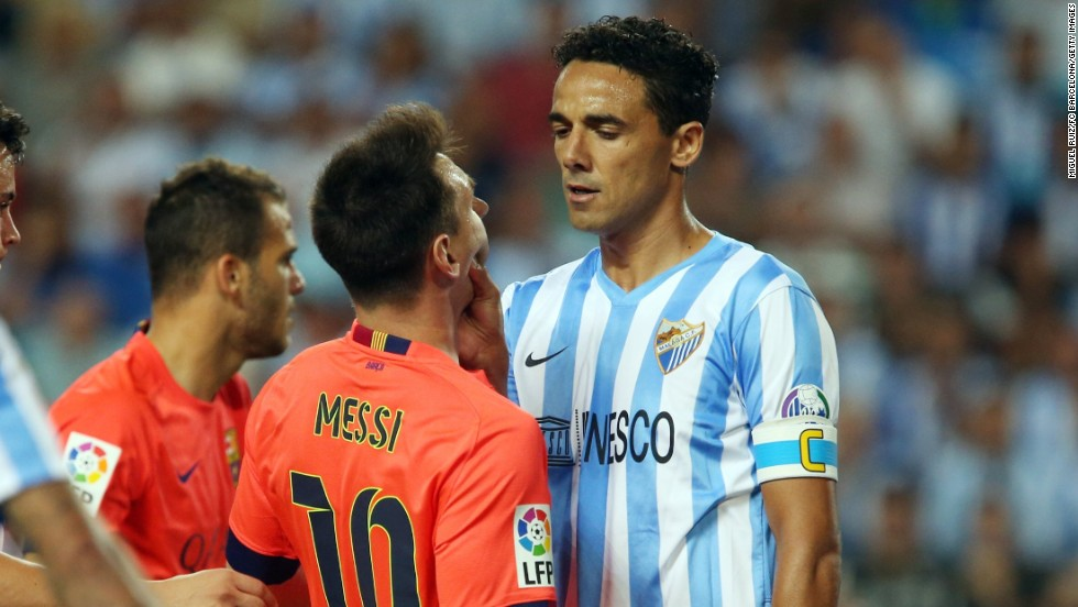 Malaga captain Wellington grabs Barcelona forward Lionel Messi during a league game in Malaga, Spain, on Wednesday, September 24. Wellington received a yellow card for the transgression.