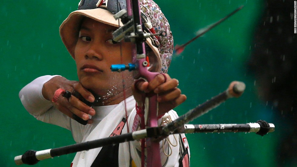 Indonesia's Diananda Choirunisa shoots an arrow in the rain during an archery match Friday, September 26, at the Asian Games in Incheon, South Korea.