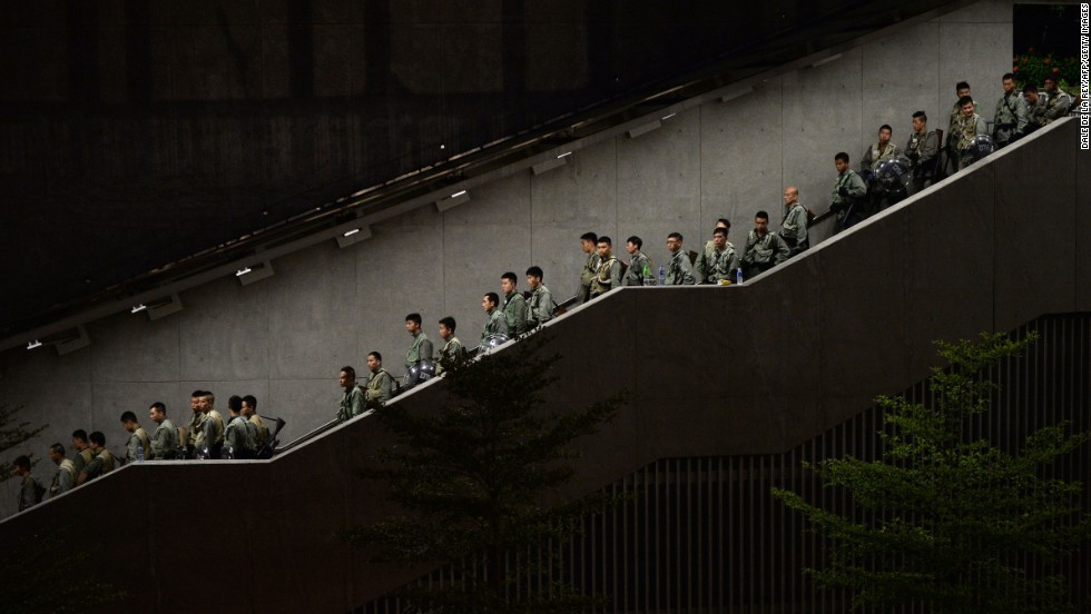Police walk down a stairwell as demonstrators gather outside government buildings in Hong Kong on September 29.