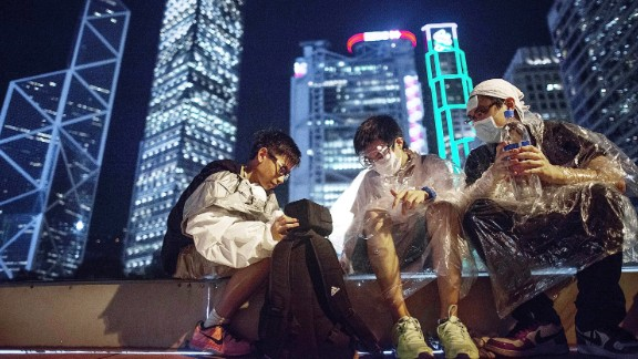 Before the distinctive backdrop of Hong Kong's high-rise skyline, protesters suit up in goggles and plastic ponchos to protect themselves against the possible use of tear gas by authorities. Demonstrators were gassed by Hong Kong police on Sunday.