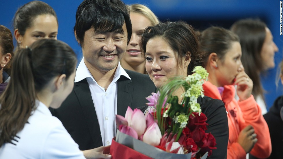 China's two-time grand slam winner Li Na, accompanied by husband Jiang Shan, accepts flowers at a ceremony to mark her  retirement.