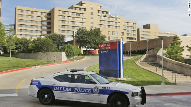 A police car drives past the entrance to the Texas Health Presbyterian Hospital in Dallas, Tuesday, Sept. 30, 2014.  A patient in the hospital is showing signs of the Ebola virus and is being kept in strict isolation with test results pending, hospital officials said Monday. (AP Photo/LM Otero)