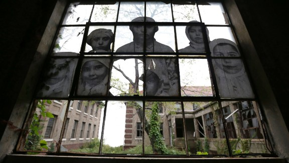 """Ellis Island -- the site of New York's """"hospital for immigrants"""" -- is offering public tours for the first time in 60 years. Original photographs of the patients and doctors of the hospital have been pasted on the crumbling walls, windows and doors."""