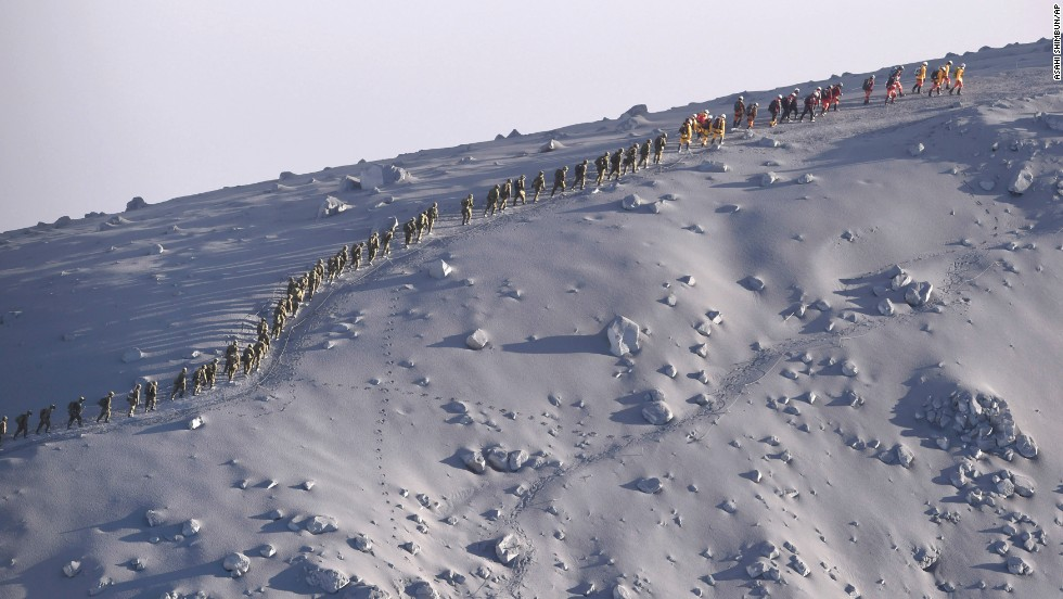 Rescuers walk in line after a search operation near the peak of Japan's Mount Ontake on Wednesday, October 1. Efforts to recover bodies from the erupting volcano have resumed after search teams had been hampered by gas and hot ash shooting into the air. At least 47 people were killed when the volcano erupted over the weekend.
