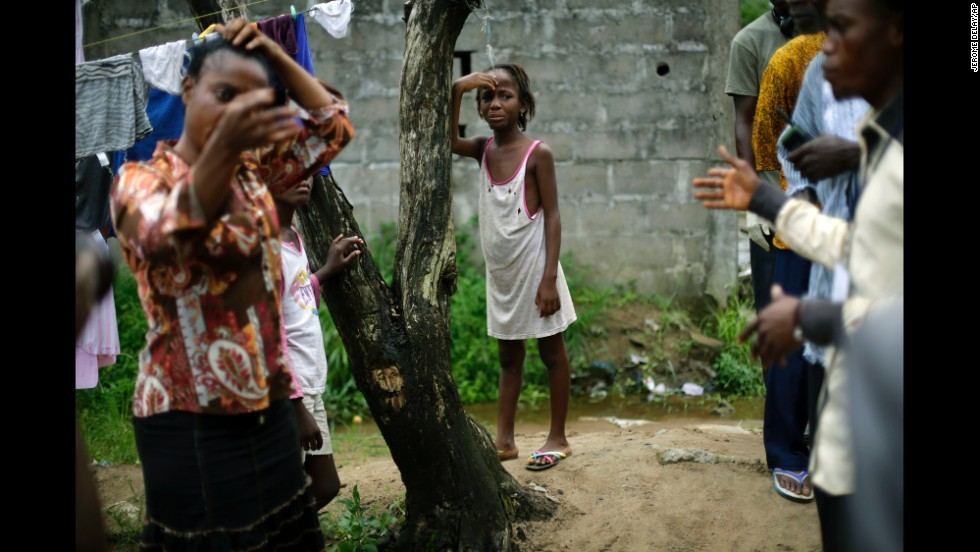 A girl cries as community activists approach her outside her Monrovia home on October 2, 2014, a day after her mother was taken to an Ebola ward.